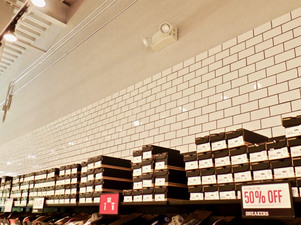 Converse store area showcasing shoes and partially tiled wall